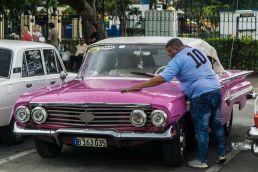 Taxista limpia carro clásico Habana